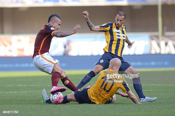 Radja Nainggolan of AS Roma battles for the ball with Emil Hallfredsson and Evangelos Moras of Hellas Verona during the Serie A match between Hellas...