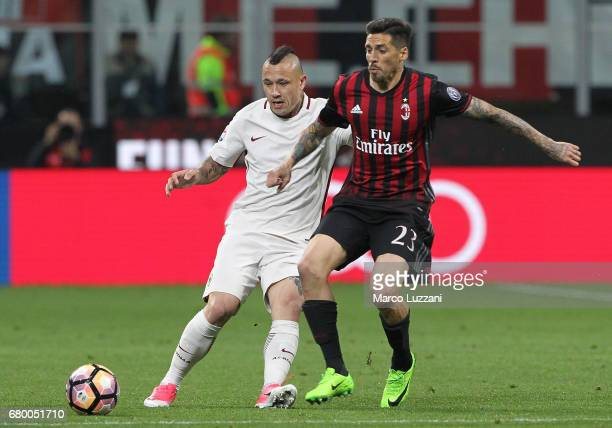 Radja Nainggolan of AS Roma competes for the ball with Jose Sosa of AC Milan during the Serie A match between AC Milan and AS Roma at Stadio Giuseppe...