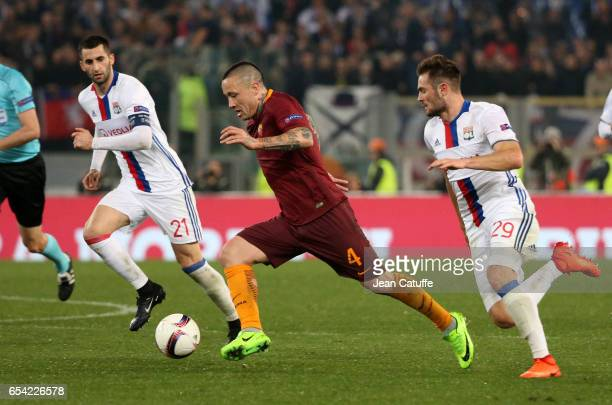 Radja Nainggolan of AS Roma in action between Maxime Gonalons and Lucas Tousart of Lyon during the UEFA Europa League Round of 16 second leg match...