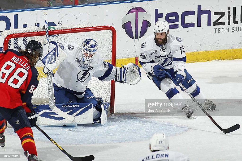 Radko Gudas #75 helps defend the net as goaltender <a gi-track='captionPersonalityLinkClicked' href=/galleries/search?phrase=Anders+Lindback&family=editorial&specificpeople=7211274 ng-click='$event.stopPropagation()'>Anders Lindback</a> #39 of the Tampa Bay Lightning stops a shot by Peter Mueller #88 of the Florida Panthers at the BB&T Center on March 12, 2013 in Sunrise, Florida. The Lightning defeated the Panthers 3-2.