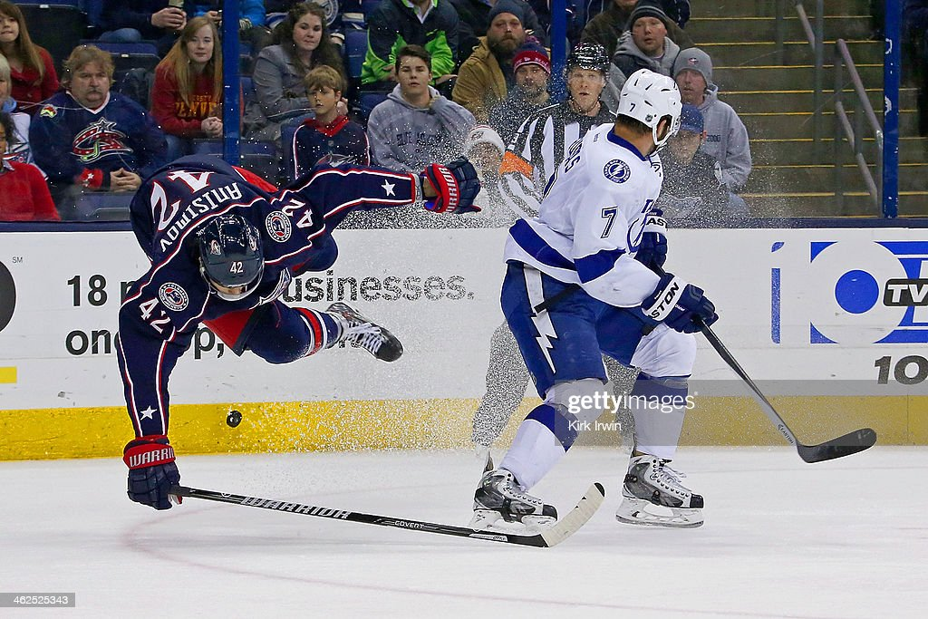 <a gi-track='captionPersonalityLinkClicked' href=/galleries/search?phrase=Radko+Gudas&family=editorial&specificpeople=5648763 ng-click='$event.stopPropagation()'>Radko Gudas</a> #7 of the Tampa Bay Lightning knocks Artem Ansimov #42 of the Columbus Blue Jackets off his feet while chasing after the puck during the second period on January 13, 2014 at Nationwide Arena in Columbus, Ohio.