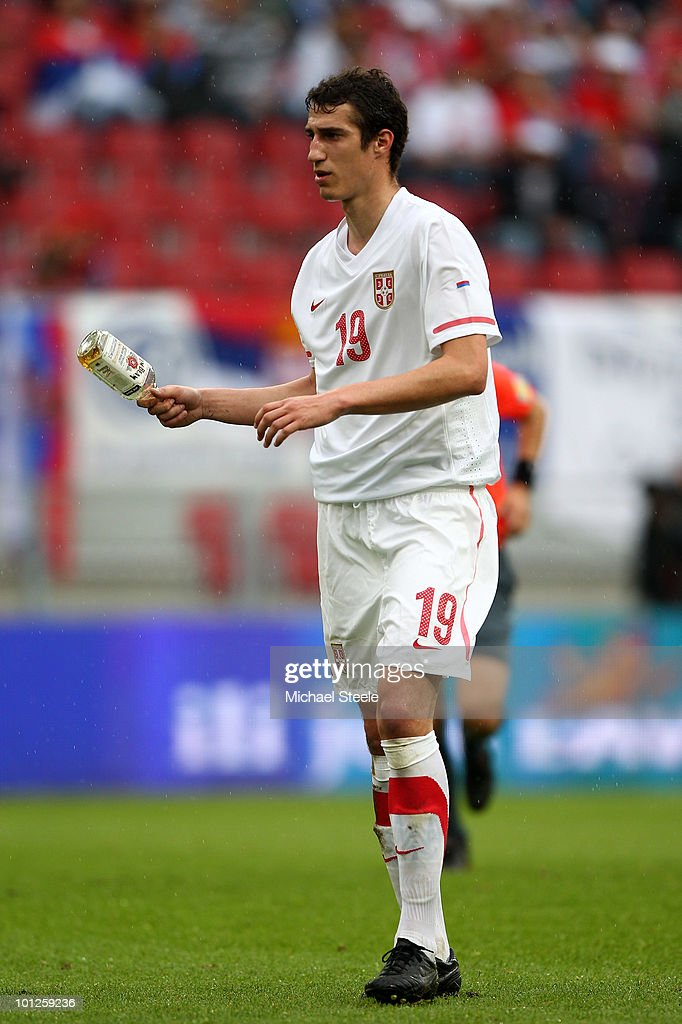 Radosav Petrovic of Serbia holds a whisky bottle after it was thrown onto the pitch by a Serbian supporter during the New Zealand v Serbia International Friendly match at the Hypo Group Arena on May 29, 2010 in Klagenfurt, Austria.