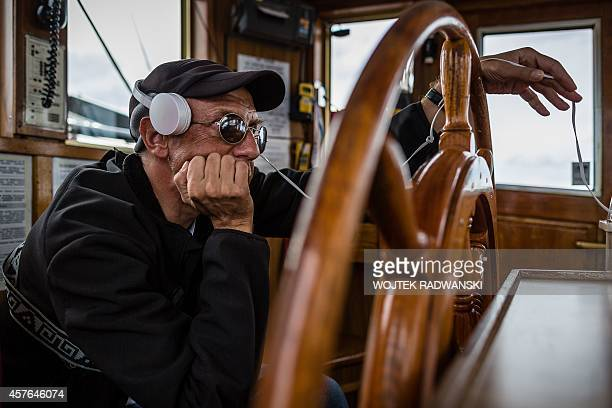 Blind Jaroslaw Gniatkowski from Poland holds the steer wheel with headphones set on his ears to hear commands from computer with information about...