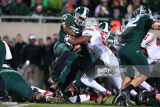 Raekwon McMillan of the Ohio State Buckeyes tackels Delton Williams of the Michigan State Spartans at Spartan Stadium on November 8 2014 in East...