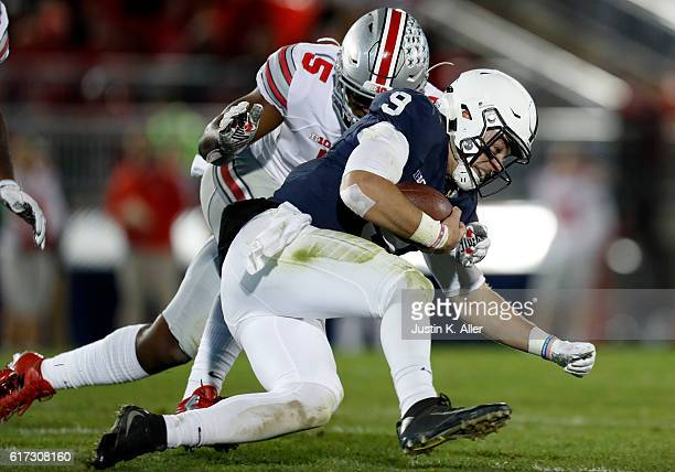 Raekwon McMillan of the Ohio State Buckeyes tackles Trace McSorley of the Penn State Nittany Lions in the first half during the game on October 22...