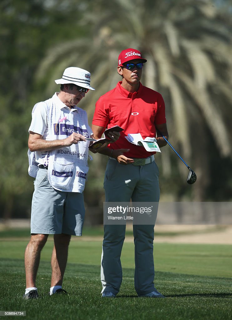 Rafa Cabrera-Bello of Spain talks with caddie Mike Batty on the 3rd hole during the third round of the Omega Dubai Desert Classic at the Emirates Golf Club on February 6, 2016 in Dubai, United Arab Emirates.