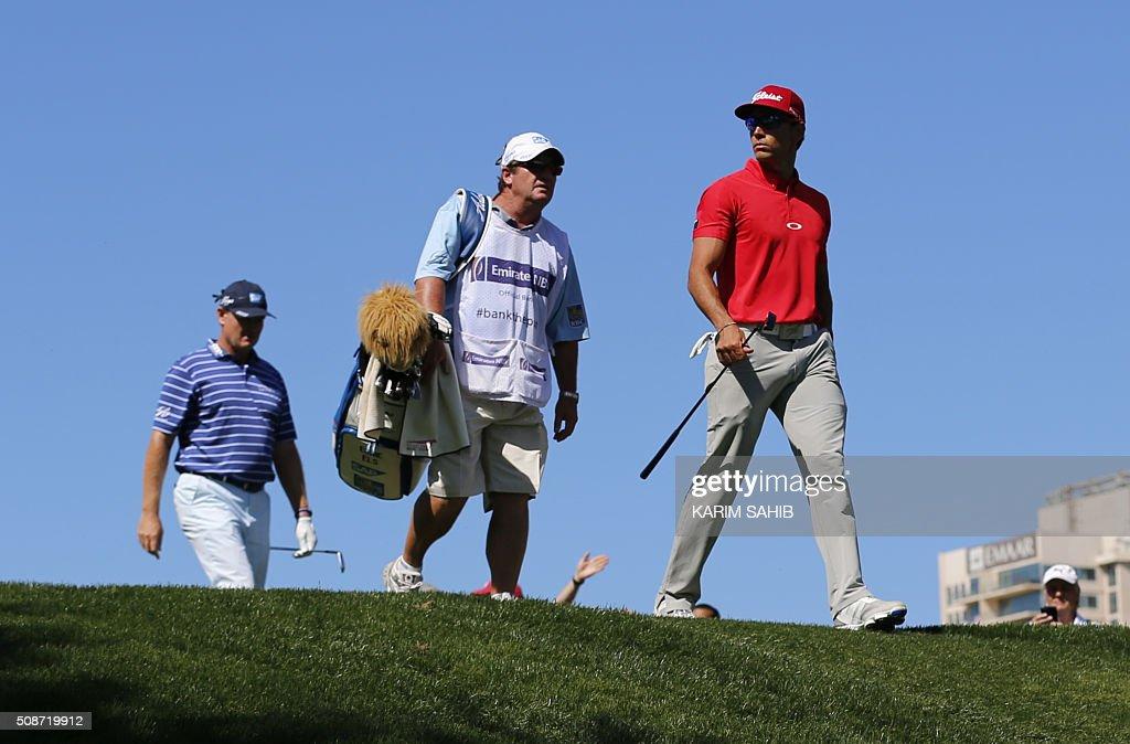 Rafa Cabrera-Bello (R) of Spain walks in the field during the third round of the 2016 Dubai Desert Classic at the Emirates Golf Club in Dubai on February 6, 2016. / AFP / KARIM SAHIB