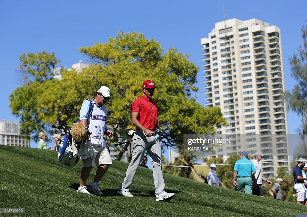 Rafa Cabrera-Bello (R) of Spain walks in the field during the third round of the 2016 Dubai Desert Classic at the Emirates Golf Club in Dubai on February 6, 2016. / AFP / KARIM SAHIB