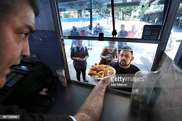 Rafael De La Fuente left serves chicken tenders and fries to Andrew Baksh from a food truck called Our Hot Sauce Truck parked at Pierce College in...
