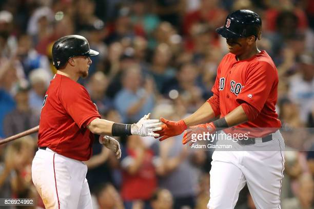 Rafael Devers high fives Christian Vazquez of the Boston Red Sox after scoring in the fifth inning of a game against the Chicago White Sox at Fenway...