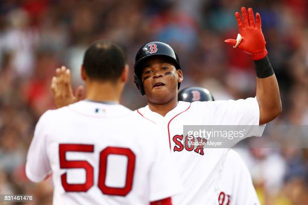 Rafael Devers of the Boston Red Sox celebrates with Mookie Betts after hitting a home run against the Cleveland Indians during the fourth inning at...