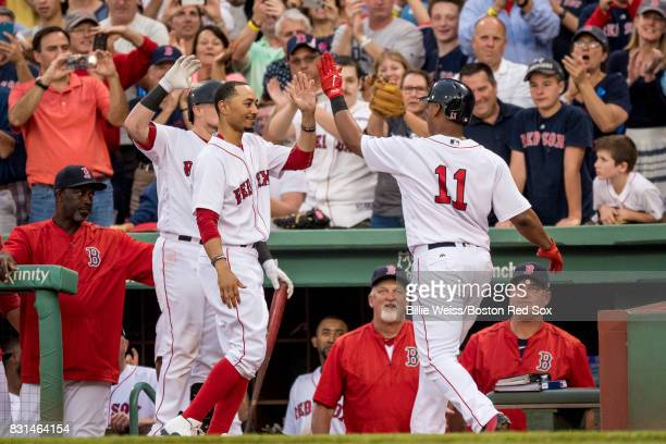 Rafael Devers of the Boston Red Sox high fives Mookie Betts after hitting a solo home run during the fourth inning of a game against the Cleveland...