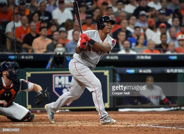 Rafael Devers of the Boston Red Sox hits a sac fly to drive in Mookie Betts in the top of the fourth inning of Game 1 of the American League Division...