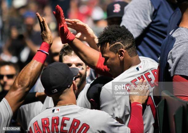 Rafael Devers of the Boston Red Sox is mobbed by teammates including Deven Marrero as they celebrate his first career hit a home run to center field...