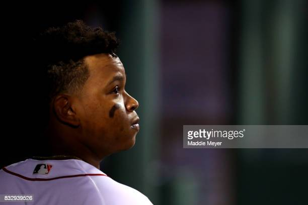 Rafael Devers of the Boston Red Sox looks on from the dugout during the third inning against the St Louis Cardinals at Fenway Park on August 16 2017...