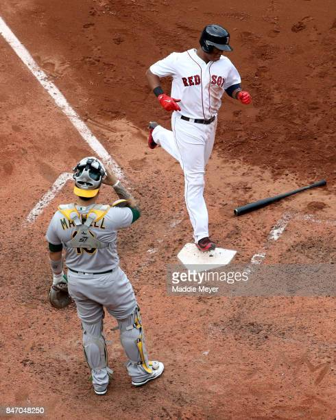 Rafael Devers of the Boston Red Sox passes Bruce Maxwell of the Oakland Athletics to score a run during the seventh inning at Fenway Park on...