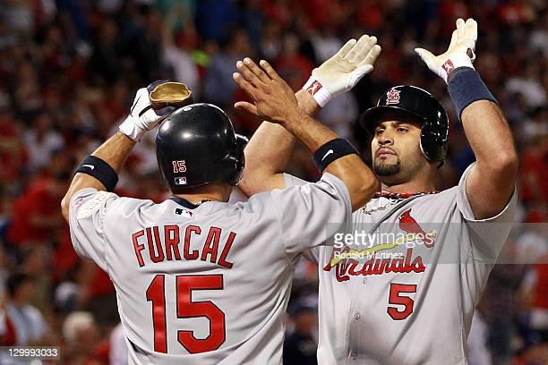 Rafael Furcal and Albert Pujols of the St Louis Cardinals celebrate after scoring on a Pujols threerun home run in the sixth inning during Game Three...