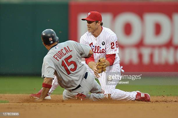 Rafael Furcal of the St Louis Cardinals slides in safe at second base after Chase Utley of the Philadelphia Phillies was unable to hold on to the...