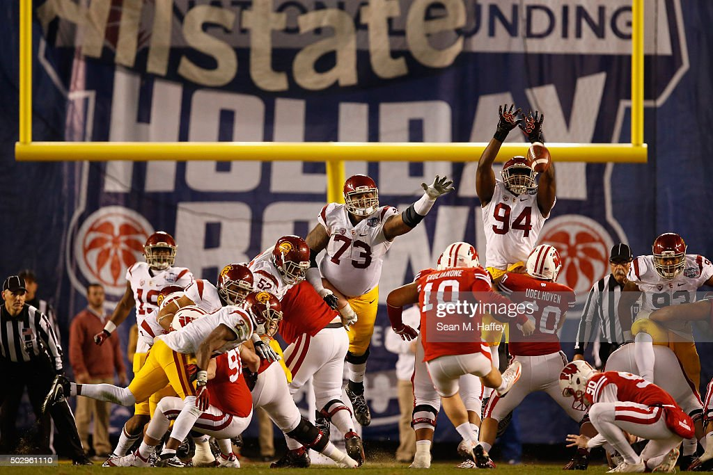 Rafael Gaglianone #10 of the Wisconsin Badgers kicks a field goal as Zach Banner #73 of the USC Trojans and Rasheem Green #94 of the USC Trojans defend during the second quarter of the National University Holiday Bowl at Qualcomm Stadium on December 30, 2015 in San Diego, California.
