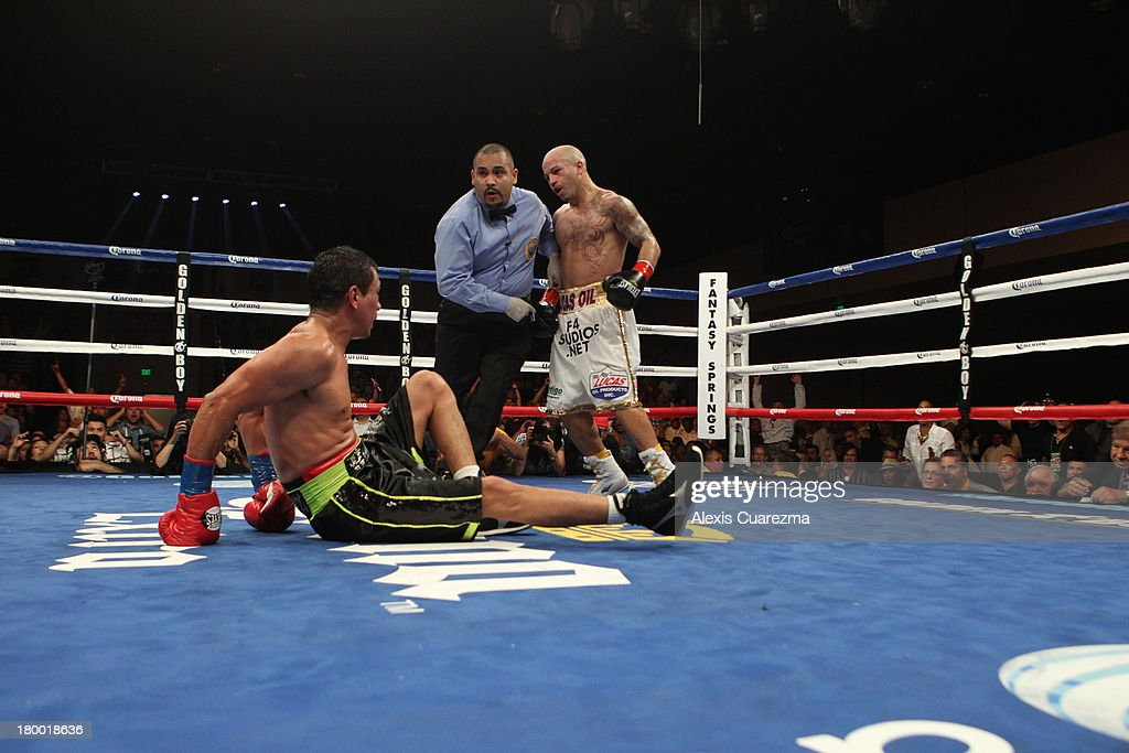 Rafael Marquez (L) is dropped to the canvas by Efrain Esquivias (R) as referee Raul Caiz Jr looks to give Marquez a ten count during their fight as the main co-event at the Fantasy Springs Resort Casino - Special Events Center on September 7, 2013 in Indio, California.