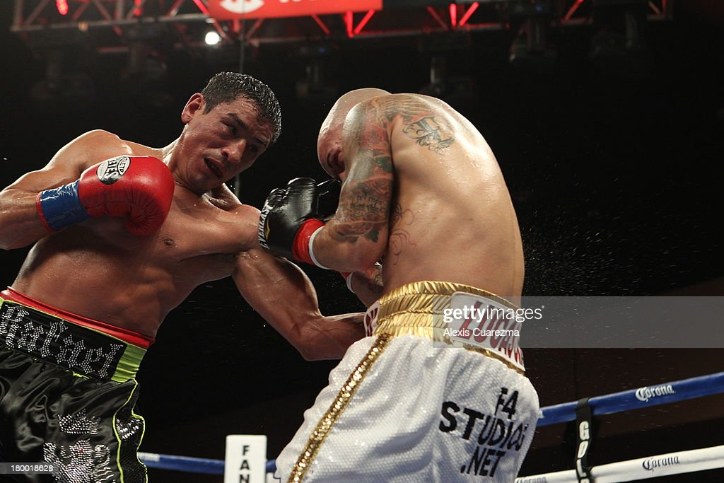 Rafael Marquez (L) lands a left body blow on Efrain Esquivias (R) during their fight as the main co-event at the Fantasy Springs Resort Casino - Special Events Center on September 7, 2013 in Indio, California.