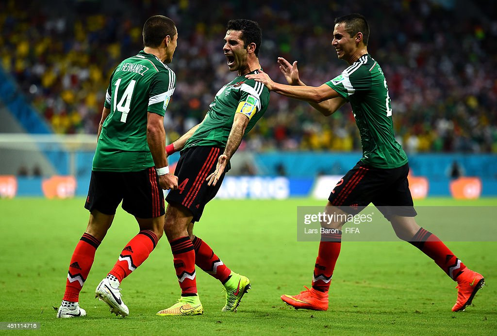 Rafael Marquez of Mexico celebrates scoring his team's first goal with his teammates Javier Hernandez and Paul Aguilar during the 2014 FIFA World Cup...
