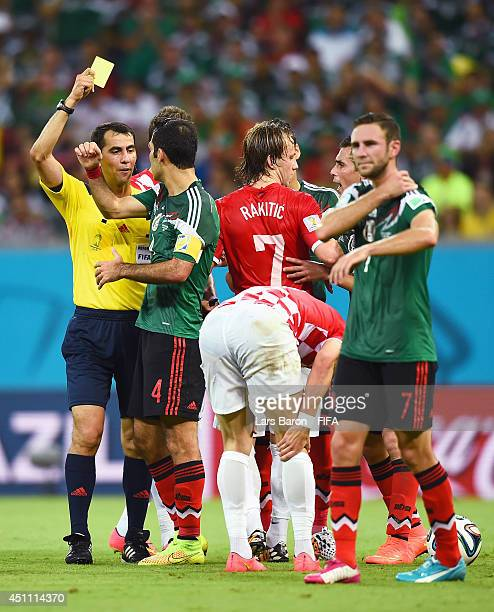 Rafael Marquez of Mexico receives an yellow card from referee Ravshan Irmatov during the 2014 FIFA World Cup Brazil Group A match between Croatia and...