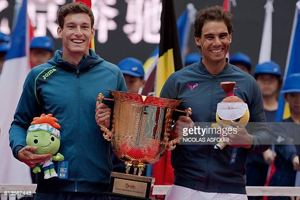 Rafael Nadal and Pablo Carreno Busta of Spain celebrate with the trophy after they beat Jack Sock of the US and Bernard Tomic of Australia in the...