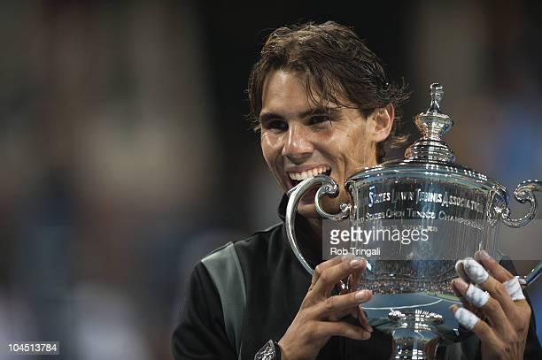 Rafael Nadal bites the US Open Trophy after defeating Novak Djokovic in the men's final on day fifteen of the 2010 US Open at the USTA Billie Jean...