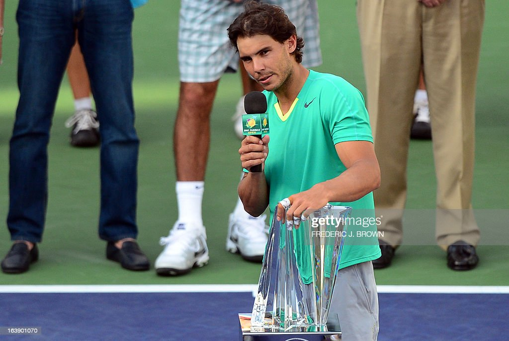 Rafael Nadal of Spain addresses the audience with a hand on the championship trophy after he defeated Juan Martin Del Potro of Argentina in three-sets on March 17, 2013 in Indian Wells, California, in the men's tennis final at the BNP Paribas Open. AFP PHOTO/Frederic J. BROWN