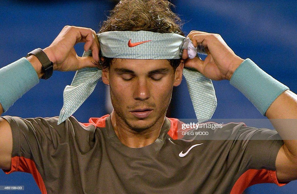 Rafael Nadal of Spain adjusts his headband between games while playing against Stanislas Wawrinka of Switzerland in the men's singles final on day 14 of the 2014 Australian Open tennis tournament in Melbourne on January 26, 2014.