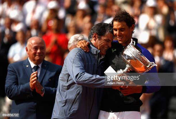 Rafael Nadal of Spain and his coach Toni Nadal celebrate with the trophy following the mens singles final against Stan Wawrinka of Switzerland on day...