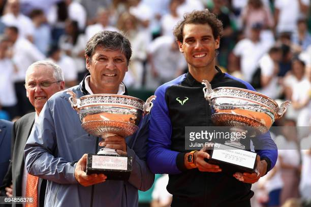 Rafael Nadal of Spain and his coach Toni Nadal pose for photos with the trophy following victory in the mens singles final against Stan Wawrinka of...