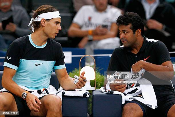 Rafael Nadal of Spain and Leander Paes of India speak between a set against Dominic Inglot of Great Britain and Robert Lindstedt of Sweden during Day...