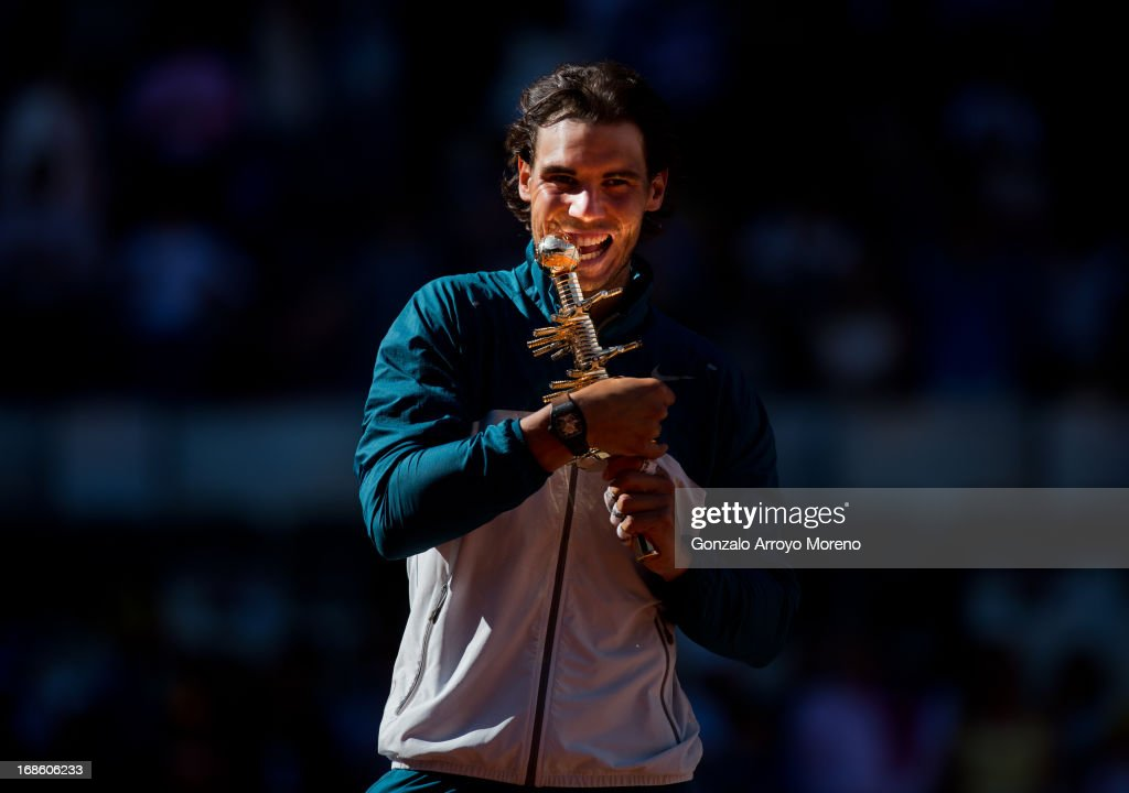 <a gi-track='captionPersonalityLinkClicked' href=/galleries/search?phrase=Rafael+Nadal&family=editorial&specificpeople=194996 ng-click='$event.stopPropagation()'>Rafael Nadal</a> of Spain bites his trophy after winning his final match against <a gi-track='captionPersonalityLinkClicked' href=/galleries/search?phrase=Stanislas+Wawrinka&family=editorial&specificpeople=557155 ng-click='$event.stopPropagation()'>Stanislas Wawrinka</a> of Switzerland on day nine of the Mutua Madrid Open tennis tournament at the Caja Magica on May 12, 2013 in Madrid, Spain.