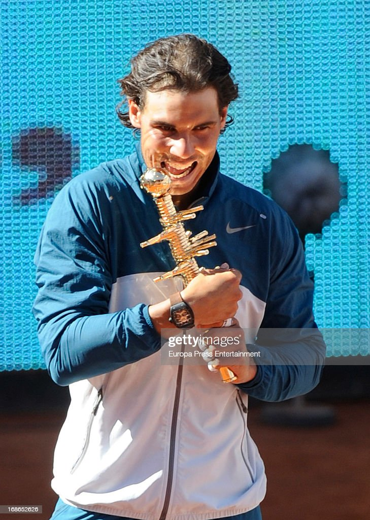 Rafael Nadal of Spain bites his trophy after winning his final match against Stanislas Wawrinka of Switzerland after the final match during the Mutua Madrid Open tennis tournament at La Caja Magica on May 12, 2013 in Madrid, Spain.