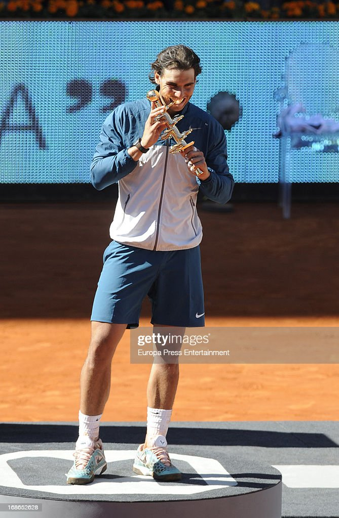 <a gi-track='captionPersonalityLinkClicked' href=/galleries/search?phrase=Rafael+Nadal&family=editorial&specificpeople=194996 ng-click='$event.stopPropagation()'>Rafael Nadal</a> of Spain bites his trophy after winning his final match against Stanislas Wawrinka of Switzerland after the final match during the Mutua Madrid Open tennis tournament at La Caja Magica on May 12, 2013 in Madrid, Spain.