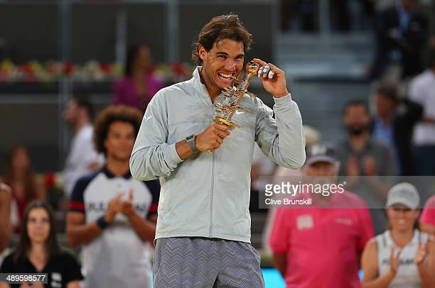 Rafael Nadal of Spain bites his winners trophy after victory over Kei Nishikori of Japan in their final match during day nine of the Mutua Madrid...