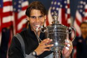 Rafael Nadal of Spain bites the championship trophy after defeating Novak Djokovic of Serbia to win the men's singles final on day fifteen of the...