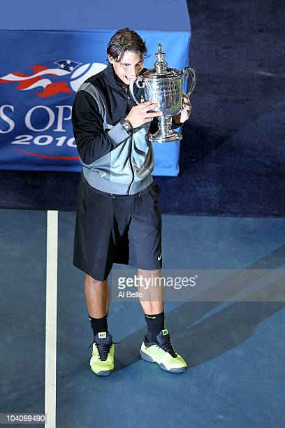 Rafael Nadal of Spain bites the championship trophy during the trophy ceremony after defeating Novak Djokovic of Serbia to win the men's singles...