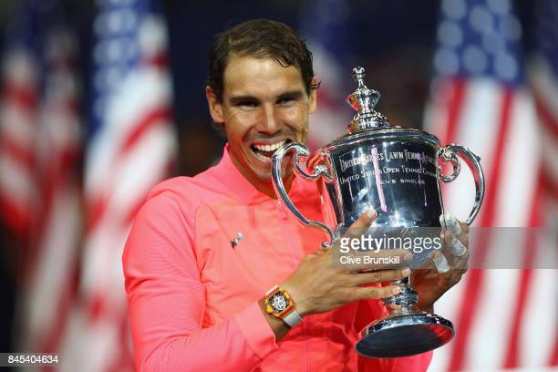 Rafael Nadal of Spain bites the championship trophy during the trophy ceremony after their Men's Singles Finals match on Day Fourteen of the 2017 US...