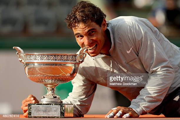Rafael Nadal of Spain bites the Coupe de Mousquetaires after victory in his men's singles final match against Novak Djokovic of Serbia on day fifteen...