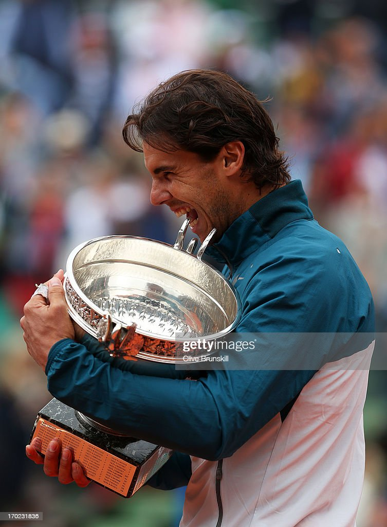 <a gi-track='captionPersonalityLinkClicked' href=/galleries/search?phrase=Rafael+Nadal&family=editorial&specificpeople=194996 ng-click='$event.stopPropagation()'>Rafael Nadal</a> of Spain bites the Coupe des Mousquetaires trophy as he celebrates victory in the men's singles final against David Ferrer of Spain during day fifteen of the French Open at Roland Garros on June 9, 2013 in Paris, France.