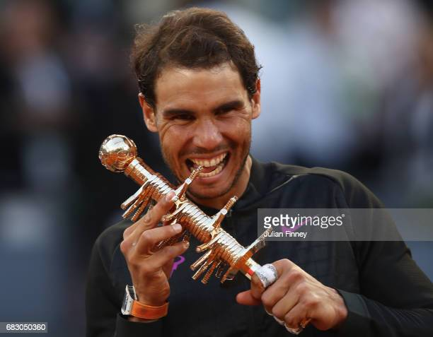 Rafael Nadal of Spain bites the winners trophy after his win over Dominic Thiem of Austria in the final during day nine of the Mutua Madrid Open...