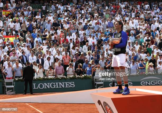 Rafael Nadal of Spain celebrates his 10th title at RolandGarros during the trophy ceremony on day 15 of the 2017 French Open second Grand Slam of the...