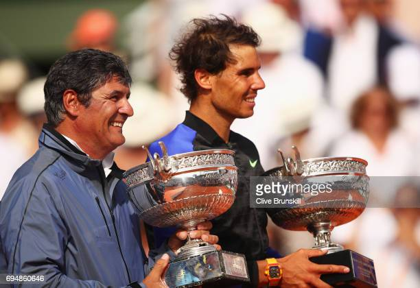 Rafael Nadal of Spain celebrates victory with the trophy alongside coach Toni Nadal after the men's singles final against Stan Wawrinka of...