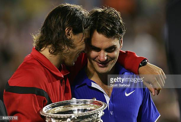 Rafael Nadal of Spain consoles Roger Federer of Switzerland during the trophy presentation after his men's final match during day fourteen of the...
