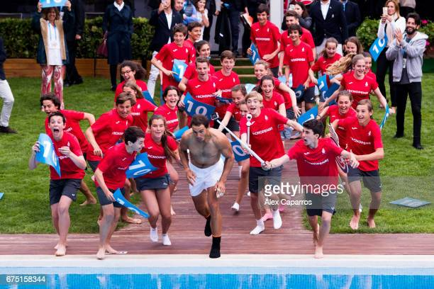 Rafael Nadal of Spain dives in the swimming pool with ballboys after his victory against Dominic Thiem of Austria in their final match on day seven...