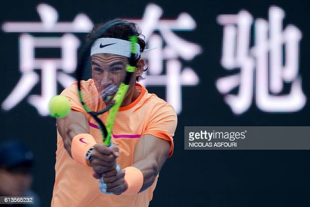 TOPSHOT Rafael Nadal of Spain hits a return during the the men's doubles final against Jack Sock of the US and Bernard Tomic of Australia of the...