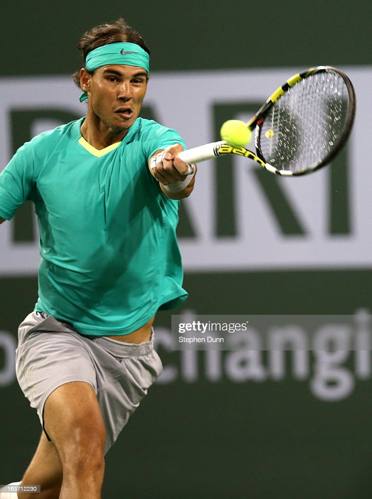 <a gi-track='captionPersonalityLinkClicked' href=/galleries/search?phrase=Rafael+Nadal&family=editorial&specificpeople=194996 ng-click='$event.stopPropagation()'>Rafael Nadal</a> of Spain hits a return to Roger Federer of Switzerland during day 9 of the BNP Paribas Open at Indian Wells Tennis Garden on March 14, 2013 in Indian Wells, California. Nadal won 6-4, 6-2.